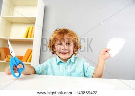 childhood and learning concept, happy kid with scissors