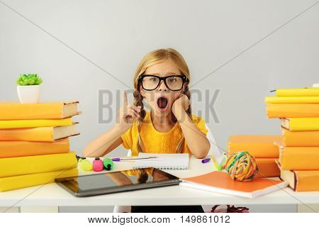 bored child yawns in front of pile of books