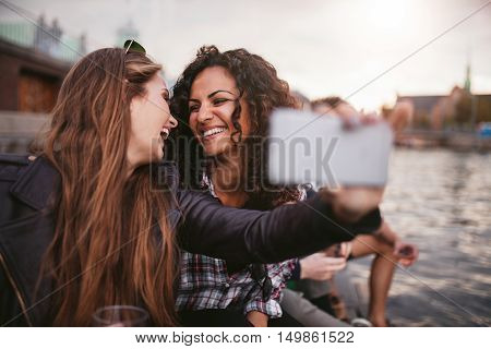 Cheerful young women friends taking selfie by the lake. Best friends having fun together.