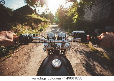 POV shot of young man riding on a motorcycle. Hands of motorcyclist on village road.