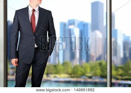 business and office concept - elegant young fashion buisness man in a blue/navy suit. Downtown behind