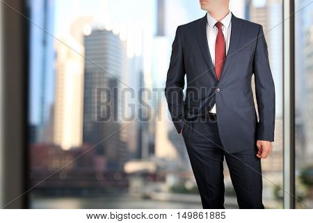 business and office concept - elegant young fashion buisness man in a blue/navy suit. Downtown background behind