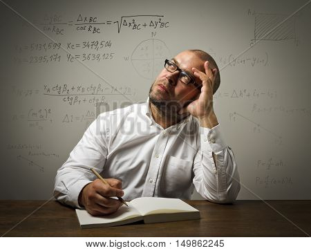 Man in white is solving equation. Scientist.