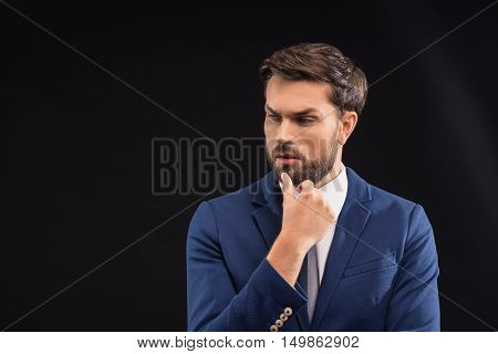 Clever young man is making serious decision. He is standing in suit and touching chin pensively. Isolated and copy space in left side