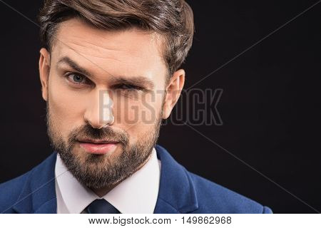 Portrait of smart businessman is staring at camera with mistrust. He is standing in suit. Isolated and copy space in right side