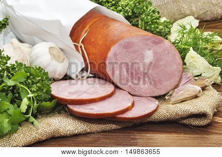 Pork Sausage Sliced In Small Pieces In A White Packing On Wooden Table.