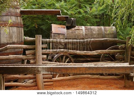 historical sluice at finding for gold with barrel and the wagon in background