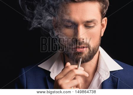 Sexy young man is smoking and looking at cigarette with desire. Isolated on black background