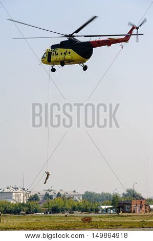 Tyumen, Russia - August 11, 2012: On a visit at UTair airshow in Plehanovo heliport. Rescuer land from MI-8 helicopter for raising of injured person