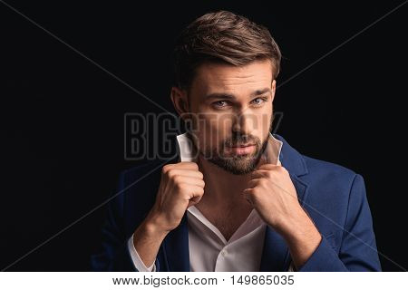 Attractive young businessman is standing and flirting. He is touching shirt collar and looking at camera with desire. Isolated