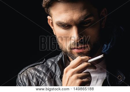 Young male smoker is making serious decision. He is standing in leather jacket. Isolated
