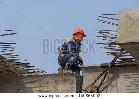 Tyumen, Russia - July 31, 2013: JSC Mostostroy-11. Bridge construction for outcome of the Tobolsk path and Bypass road round Tyumen. Builder works in safety protective equipment on bridge construction