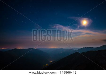 Moonrise over clouds in Fagaras mountains in Romania