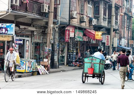 Shanghai China - October 22 2006: People in a street on the outskirts of Shanghai with shops and dwellings