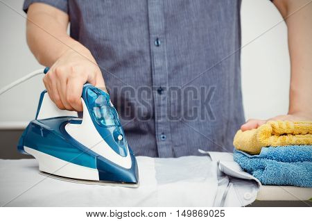 Man irons clothes on ironing board with steaming blue iron
