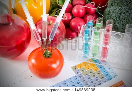 Three Syringes In Red Tomato. Genetically Modified Food Concept.