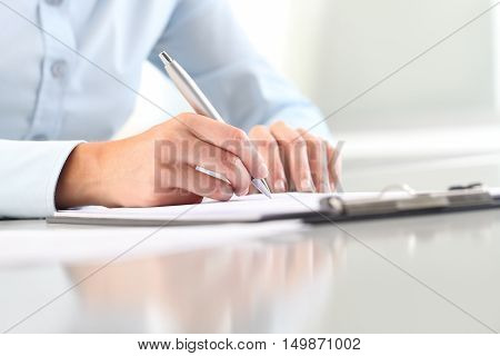 Woman's hands writing on sheet in a clipboard with a pen; isolated on desk