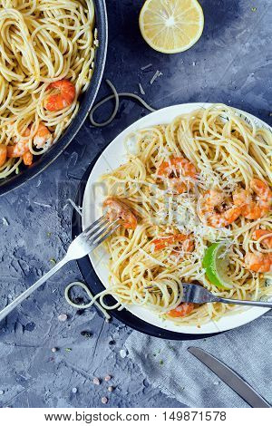 Pasta spaghetti with shrimps and parmigiano reggiano cheese. Top view, vertical. Concrete background
