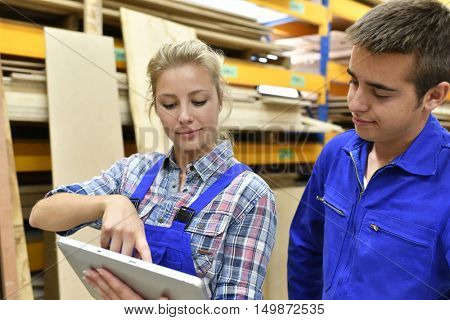 Young people in carpentry apprenticeship using tablet