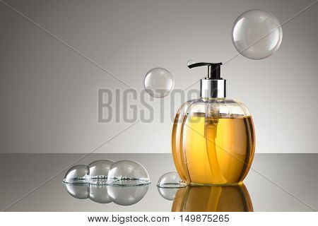 Beautiful bottle of liquid hand soap with bubbles on a reflective surface