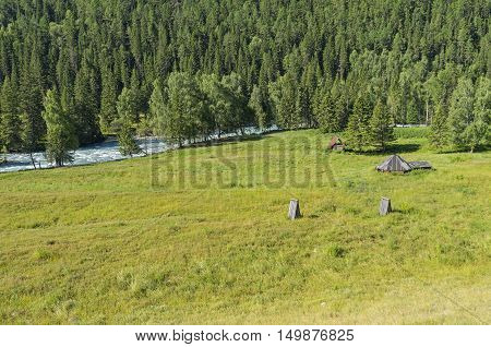 Abandoned cattle-ranch on the banks of river Kucherla. Altai Mountains Russia. Sunny summer day.
