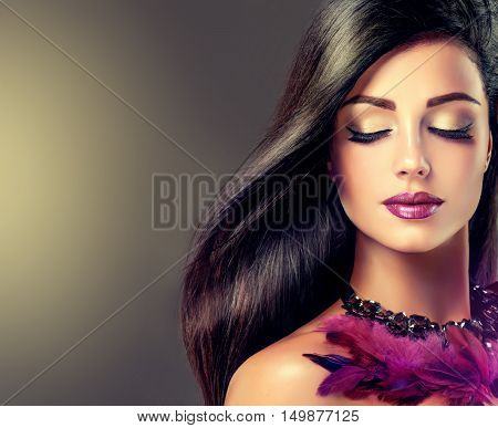Beautiful brunette girl  model with long straight  black hair . Jewelry necklace purple feathers .