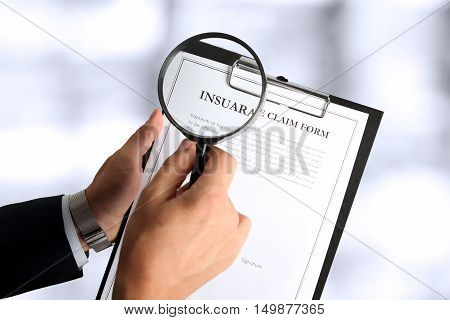 man looking through a magnifying glass to the Blank insurance claim form