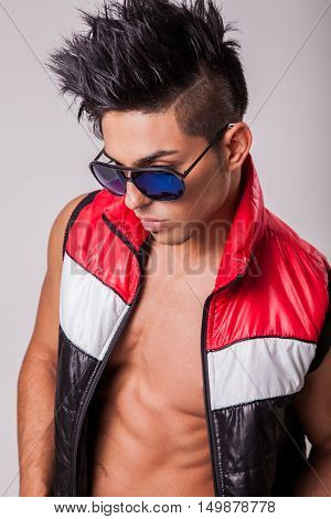 Young sexy middle eastern fashion model with fashion hairstyle posing and undressing to show his sexy body.