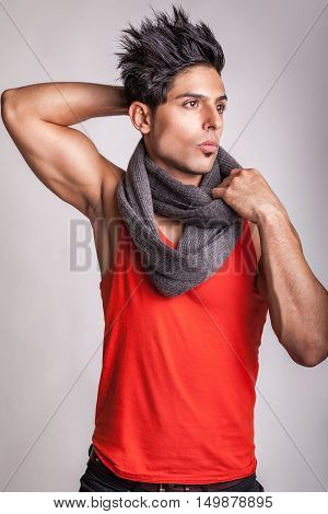 Fashion middle eastern model with scarf posing with his muscular body in studio on gray background.