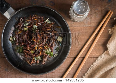 Fried grasshopper with pandan Season with salt pepper and soy sauce. on old wooden table
