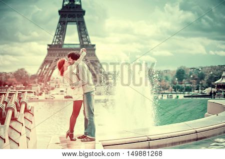 Travel Europe. Lovers kissing in Paris with the Eiffel Tower in the Background. Toning in trendy filters color. Style vintage postcards