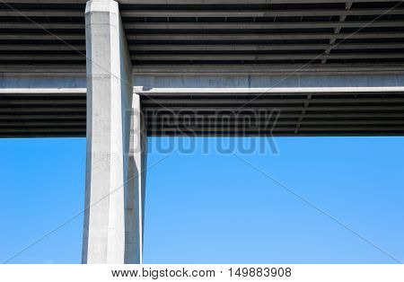 Underside of large concrete highway bridge and pylons at right angle against clear blue sky.