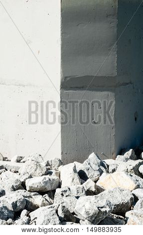Uneven rock and gravel rubble by smooth gray concrete wall corners with varied illumination.