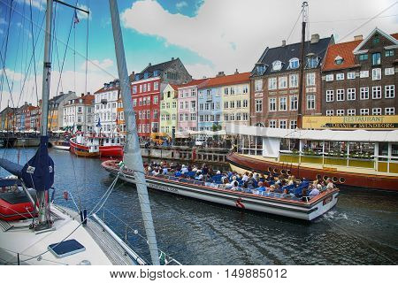 Copenhagen Denmark - August 15 2016: Tourists enjoy and sightseeing in tourist boat at the canal Nyhavn. The boat is loaded with sightseeing tourist people in Copenhagen Denmark