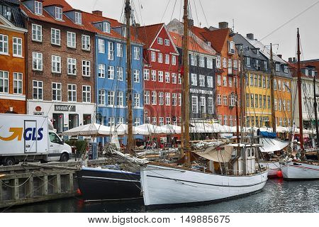 COPENHAGEN DENMARK - AUGUST 15 2016: Boats in the docks Nyhavn people restaurants and colorful architecture. Nyhavn a 17th century harbour in Copenhagen Denmark on August 15 2016.