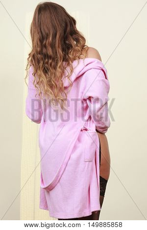 Subtlety and sexiness. Lovely attractive woman wearing black lingerie and pink negligee dressing gown. Sexy lady in lacy underwear.