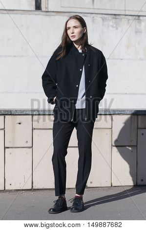 young female fashion model in black bomber jacket gray shirt and black boots - street style