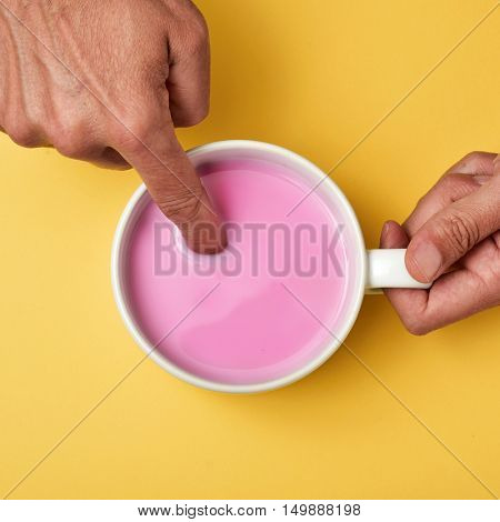 high-angle shot of a young caucasian man soaking his forefinger in a pink milkshake, on a yellow surface