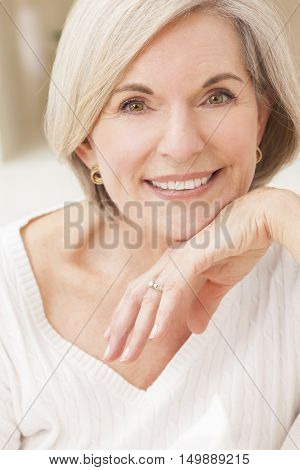 Portrait of an attractive elegant senior woman relaxing at home.