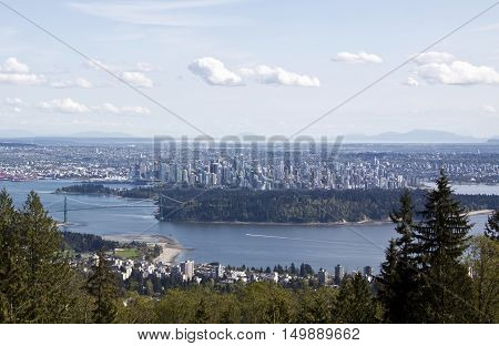 View of downtown Vancouver with condos and building seen on the West Vancouver side where the shot was taken atop Cypress Bowl Drive. It looks across Burrard Inlet and past Stanley Park with a full view of the Lions Gate Bridge on a beautiful bright sunny