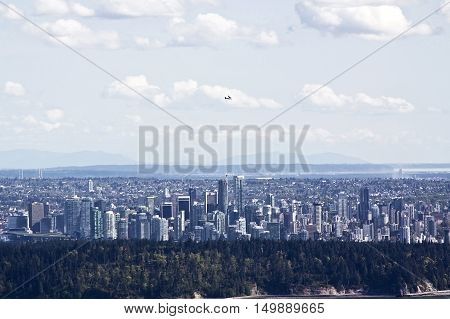 Straight on view of downtown Vancouver with a small plane flying overhead from atop Cypress Bowl Drive in West Vancouver BC looking across Burrard Inlet past Stanley Park on a beautiful bright sunny day in April.