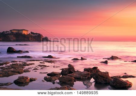 Castiglioncello travel destination old building on the rocks and sea on sunset. Tuscany Italy Europe. Long Exposure