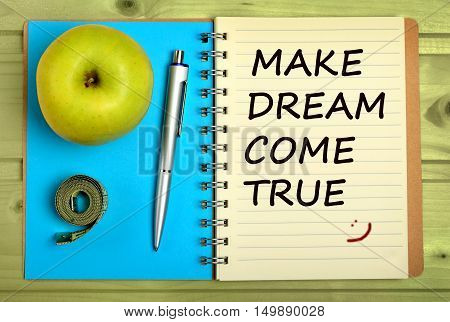 Make dream come true.Inspirational quote on notebook