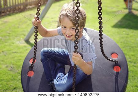 Young boy playing on a swing in the summer sunshine