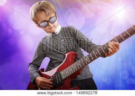 Boy playing electric guitar on stage in rock music school talent show