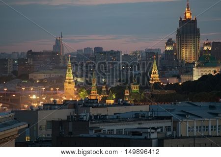 Stars on Kremlin towers among roofs, Stalin skyscraper in center of Moscow, Russia at night