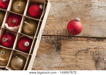 Boxed assortment or red and gold Christmas baubles with a single red one outside the packaging on a rustic wooden background with copy space