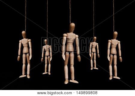 Low key, group of wooden marionettes puppet hangman by rope, on black background