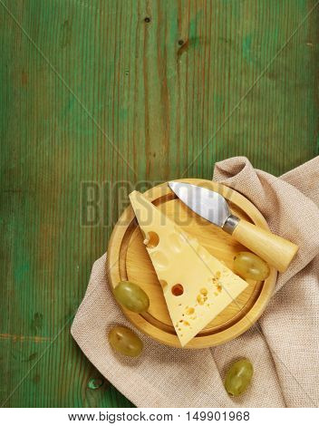 natural cheese Maasdam on a wooden table