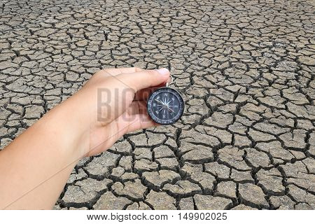hand of a man holding a compass and cracked land in the countrysideconcept of journey and aridity.